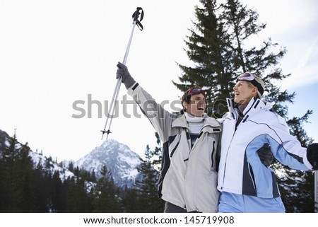 Cheerful skiing couple in warm clothing with skis against mountains - stock photo