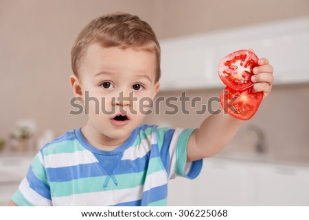 Cheerful small boy is holding pieces of chopped tomato. He is showing it to the camera and looking forward with interest - stock photo