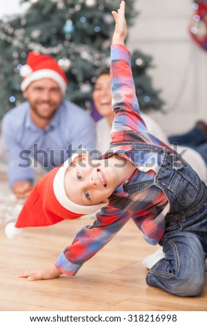 Cheerful small boy is sitting on flooring and posing near New Year tree. He is wearing red hat. His parents are lying behind him and looking at son with joy. They are laughing - stock photo