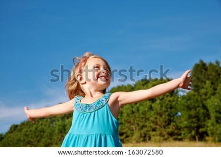 Cheerful small girl enjoying summertime  - stock photo