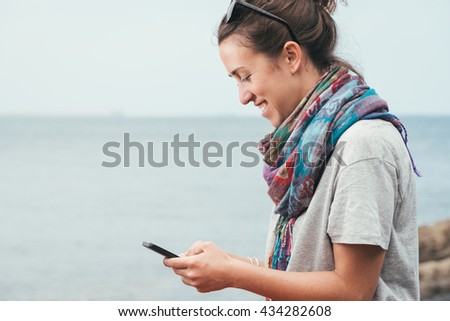 cheerful smiley woman by the sea texting on phone with sunglasses on summer - stock photo