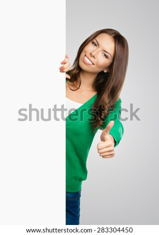 Cheerful smiling beautiful woman in green casual clothing, showing blank signboard or copyspace for slogan or text, with thumb up gesture, against grey background - stock photo