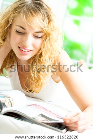 Cheerful smiling blond woman reading magazine - stock photo