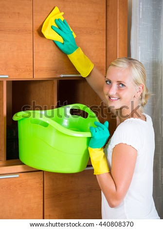 Cheerful smiling blonde girl in rubber gloves cleaning indoors  - stock photo