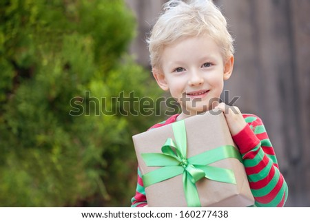 cheerful smiling boy holding his christmas present at christmas time - stock photo
