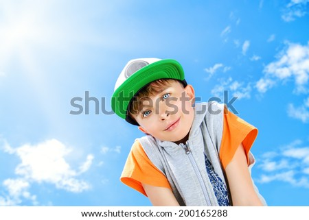 Cheerful smiling boy looking at the camera against the blue sky. Summer.  - stock photo