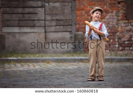 Cheerful smiling boy with baguette outdoors - stock photo