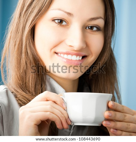 Cheerful smiling business woman drinking coffee at office - stock photo