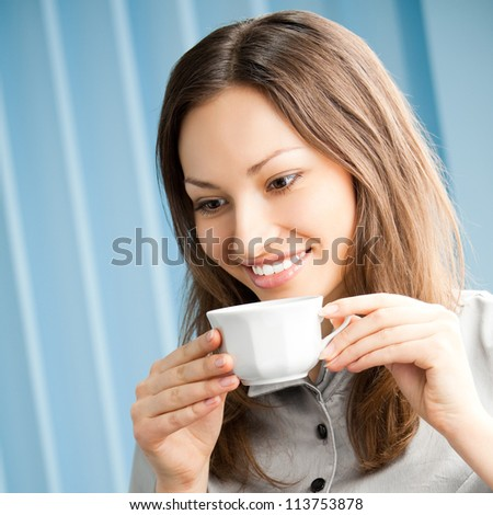 Cheerful smiling business woman drinking coffee at office