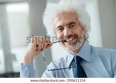 Cheerful smiling businessman portrait, he is holding glasses and looking at camera - stock photo