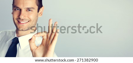Cheerful smiling businessman with okay gesture, with blank copyspace area for text or slogan, specially toned - stock photo