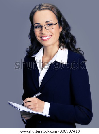 Cheerful smiling businesswoman in black suit with notepad or organizer,  posing at studio, over