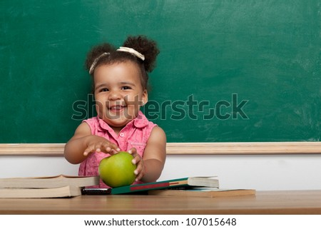 Cheerful smiling child (girl) at the blackboard. School concept - stock photo