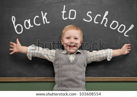 Cheerful smiling child  stands at the blackboard. Looking at camera. School concept - stock photo
