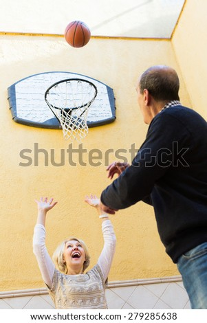 Cheerful smiling couple of pensioners playing basketball in patio - stock photo