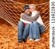 Cheerful smiling couple swinging in hammock on backyard - stock photo
