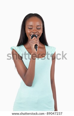 Cheerful smiling female singer against a white background - stock photo
