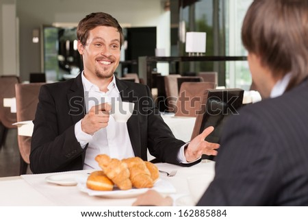 Cheerful smiling funny business man talking to his friend. Drinking coffee with donuts  - stock photo