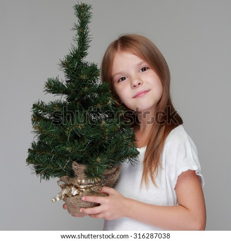 Cheerful smiling girl with long hair and a white dress holding a Christmas tree for Christmas and New Year - stock photo