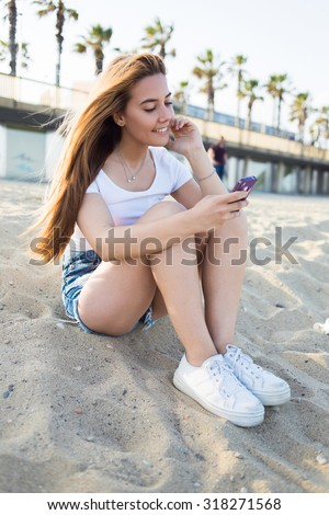 Cheerful smiling hipster girl reading message on smart phone while sitting on coast against tropical sky, charming happy woman looking her funny photos on cell telephone while resting on the beach - stock photo