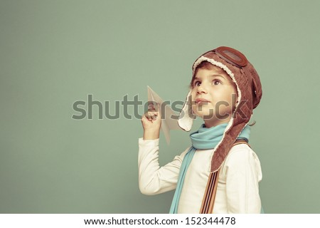 Cheerful smiling kid (boy)l in helmet on a green background. Vintage pilot (aviator) concept - stock photo