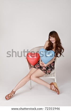 Cheerful smiling lady holding heart shaped balloon and sitting on chair. - stock photo