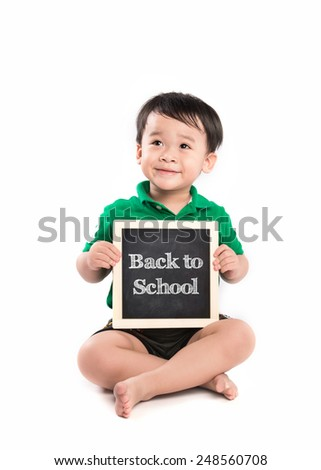 Cheerful smiling little asian boy on a white background. Looking at something. School concept. Happy child holding black board. Isolated. Back To School - stock photo