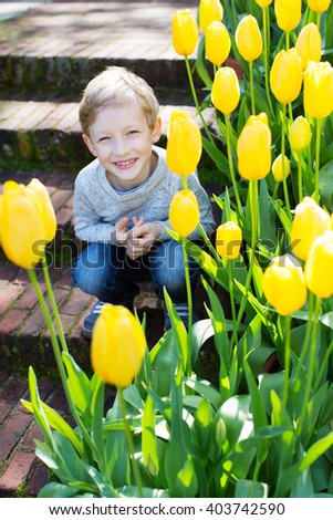 cheerful smiling little boy enjoying warm spring weather in the blooming park  - stock photo