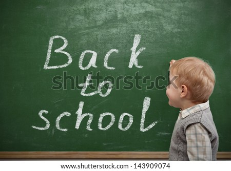 Cheerful smiling little boy on a green background. Looking at camera. School concept - stock photo