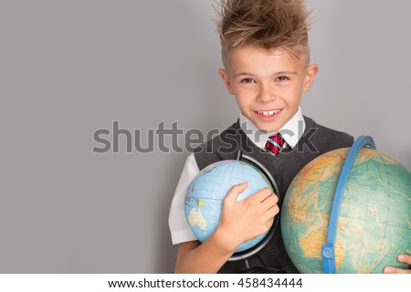 Cheerful smiling little boy on a grey background. Looking at camera. School concept - stock photo