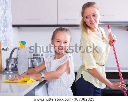 Cheerful smiling little girl helping happy mother doing cleanup at kitchen