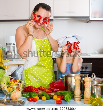 Cheerful smiling little girl with mom cutting vegetables for soup at home kitchen - stock photo