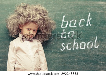 Cheerful smiling little kid (boy) against chalkboard. Looking at camera. Little Einstein style. School concept - stock photo