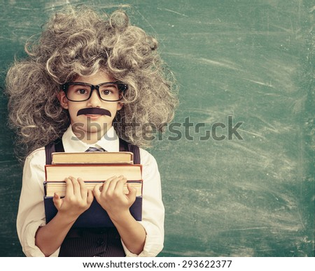 Cheerful smiling little kid (boy) against chalkboard. Looking at camera. Little Einstein style. School concept