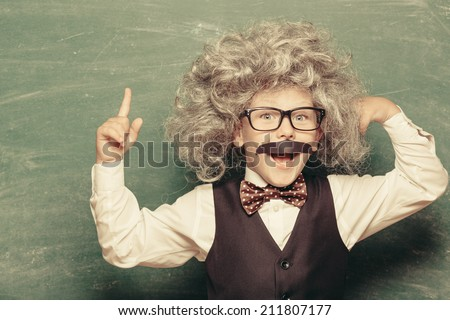 Cheerful smiling little kid (boy) against chalkboard. Looking at camera. Little genius style. School concept