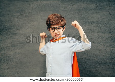 Cheerful smiling little kid (boy) against  chalkboard raised his hands up.  School and superhero concept - stock photo