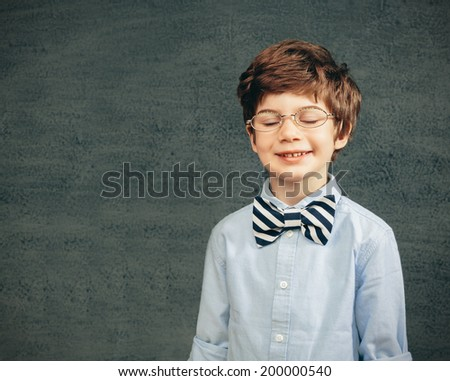 Cheerful smiling little kid (boy) against  chalkboard.  School concept