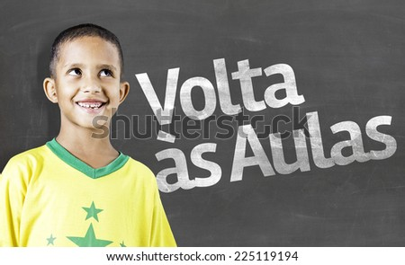 Cheerful smiling little kid (boy) against chalkboard. School concept. Back to School (In Portuguese: Volta as Aulas) - stock photo