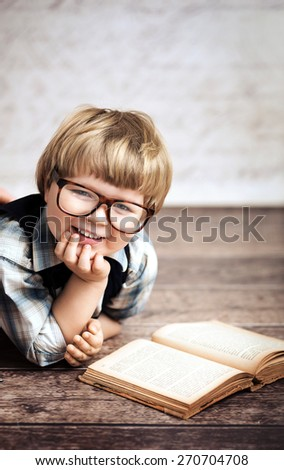 Cheerful smiling little kid reading a book - stock photo