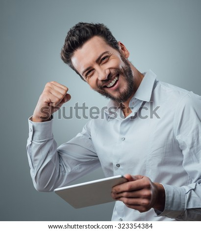 Cheerful smiling man receiving good news on tablet with fist raised - stock photo