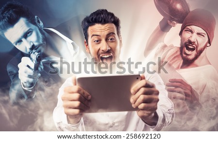 Cheerful smiling man watching videos and playing video games on his tablet - stock photo