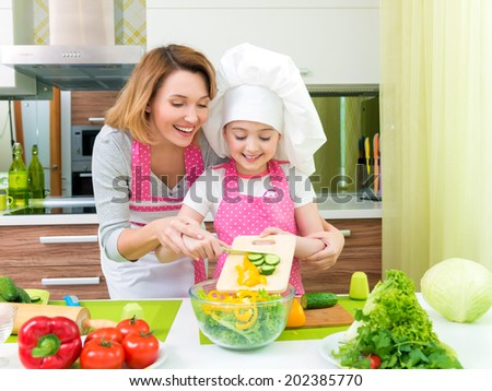 Cheerful smiling mother and daughter cooking a salad at the kitchen. - stock photo