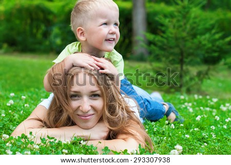 Cheerful Smiling Mother with Boy playing with Her Hair. Sitting on Back. Lifestyle concept.  - stock photo