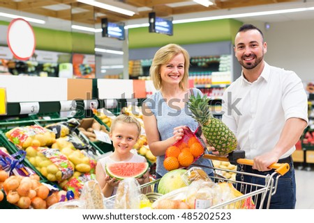 Cheerful smiling parents with little daughter choosing fruits in hypermarket
