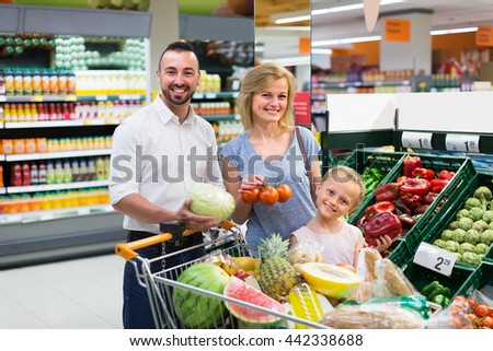 Cheerful smiling parents with little girl picking vegetables in food store