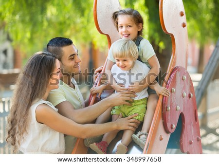 Cheerful smiling parents with two daughters playing at children's slide