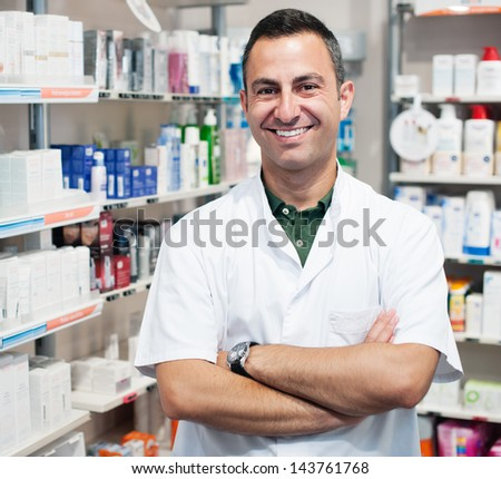 cheerful smiling pharmacist chemist man standing in pharmacy drugstore - stock photo