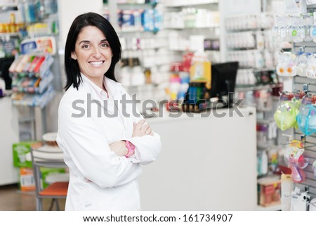 cheerful smiling pharmacist standing in pharmacy drugstore