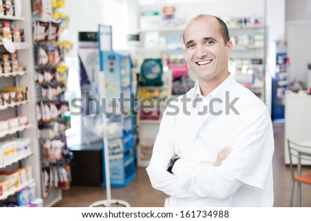 cheerful smiling pharmacist standing in pharmacy drugstore - stock photo