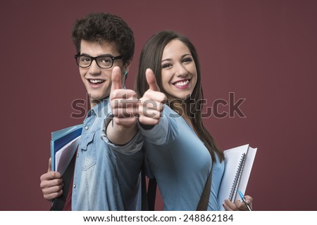 Cheerful smiling students thumbs up and holding textbooks - stock photo